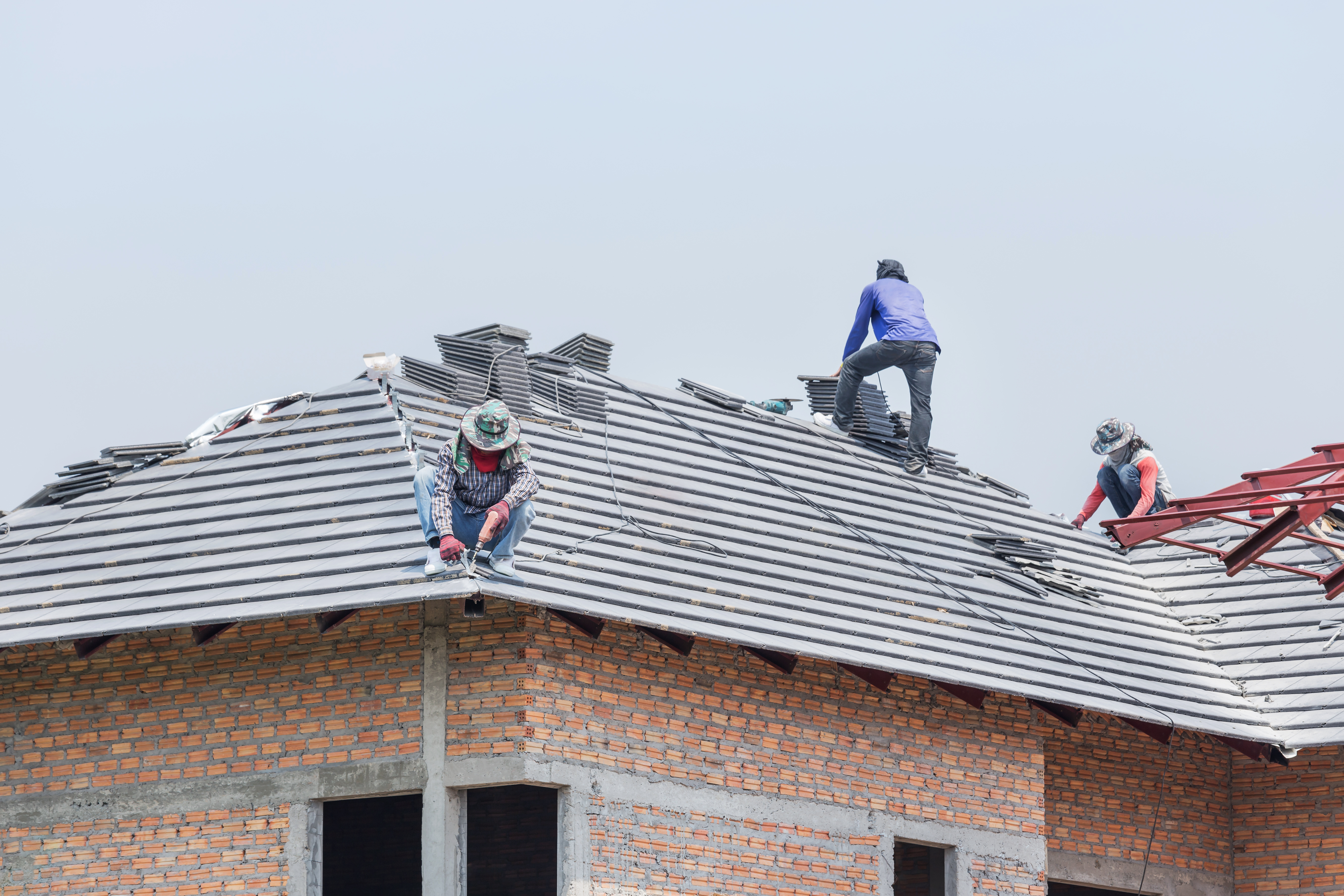 Workers installing concrete tiles on the roof while roofing house in construction site